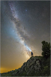 Yuri Zvezdny - Man shining a flashlight on the Milky Way from atop a mountain in Russia.